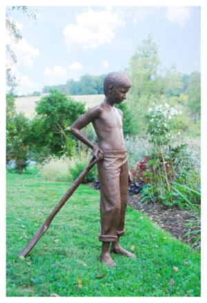 Life-size bronze sculpture of a boy with spade in a garden