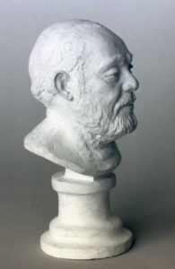 Realistic plaster sculpture - a bust of an elderly bearded man on a pedestal