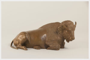 Table size bronze sculpture of a buffalo reclining