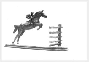 Table-size realistic bronze sculpture of a timber race horse taking off to clear a five foot fence