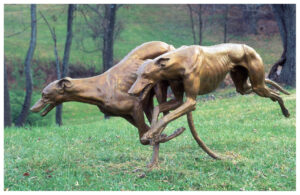 Realistic life-size bronze sculpture of two greyhounds, one in full tuck turning right and the other in full extension in midair