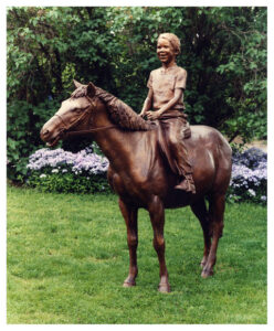 Realistic bronze sculpture life-size of a beaming young girl on her pony