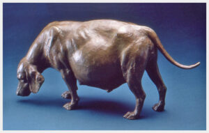 Realistic bronze sculpture table-size of a very pregnant beagle with her head sniffing the ground