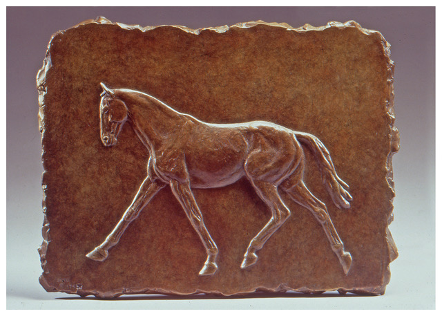 Realistic bronze bas relief sculpture plaque of a horse in an extended trot