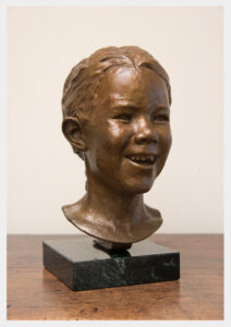 Realistic bronze sculpture of a girl with a snaggle toothed smile, hair in a braid