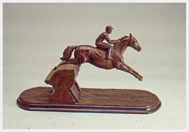 Realistic bronze sculpture of a horse with both front legs extended as it skims over a brush fence with a jockey riding.