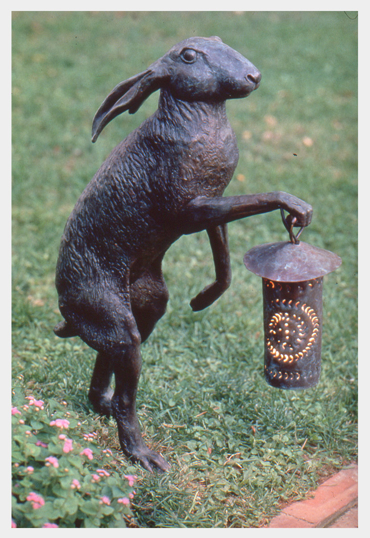 Realistic bronze sculpture of a jack rabbit standing on its hind legs holding an old-fashioned punched copper lantern which has been electrified in its right front paw