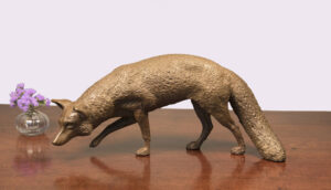 Realistic bronze sculpture table size of a red fox hunting right front leg up tail to the left head down scenting while looking ahead.