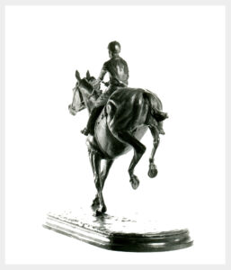 Realistic bronze sculpture of a horse landing on its front legs after jumping hind legs still flexed in the air. Rider leaning back reins loose. Sculpture on a base.