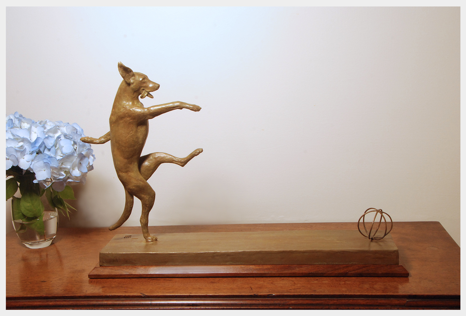 Realistic bronze sculpture on a base of a dog balanced on her right hind leg kicking a ball with her left hind foot front legs helping her balance looking forward mouth open tongue lolling out to right