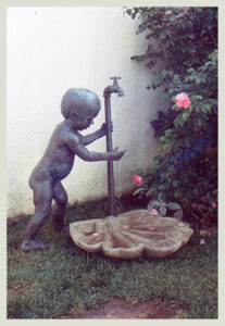 Realistic bronze sculpture of a toddler grasping water dripping from a faucet dripping into a concrete shell life-size