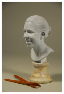 Realistic bronze sculpture with a white patina of a young woman smiling, with her hair in a bun