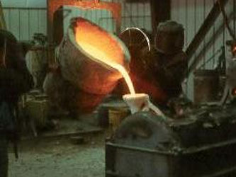 Pouring the molten bronze, approximately 2300 degrees Fahrenheit, into the porcelain molds. The porcelain molds can withstand such high temperatures and thermal shock and do not break.