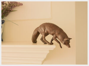 Realistic mantel-piece sized bronze sculpture of a fox starting to jump off a structure.