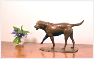 Table-size bronze sculpture of a happy Labrador Retriever right foot extended