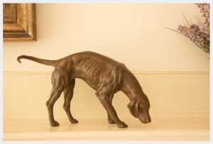 Realistic bronze sculpture of a hound table size with his nose to the ground